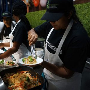 High school chefs plate noodles at the Royal High School Chef Competition