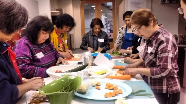 Community members prepare biryani together at 'Cooking With Joy'