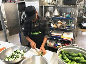 Staff cutting cucumbers on kitchen countertop.