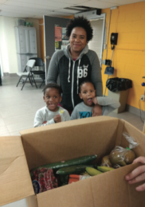 A family smiles standing by a Good Food Box