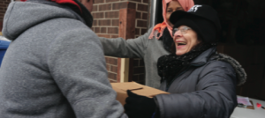 Person smiles, receiving a Good Food Box
