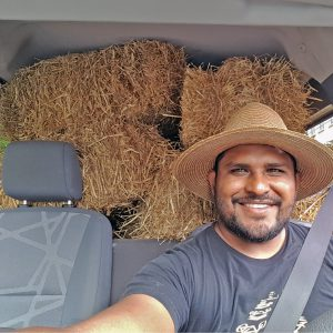 Portrait of Orlando sitting in a car, the rear seats hold hay